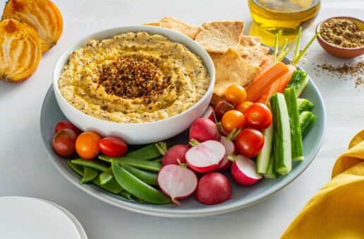 golden-beet-hummus-served-with-vegetable-sticks-and-topped-with-quinoa-and-arugula