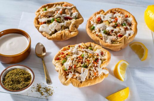 baked-pita-bowls-stuffed-with-mediterranean-style-chicken-rice-peas-carrots-bell-peppers-and-tahini-sauce